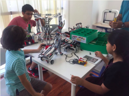 Premier Genie summer camp students with robotics around white table